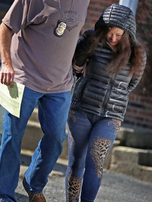 Tsui-Hsueh Wang is escorted out of the business at 5550 W. 10th St. after a raid on the massage parlor, Friday, March 2, 2018.  The owner is being arrested on charges of prostitution and promoting prostitution after the morning raid on the business.