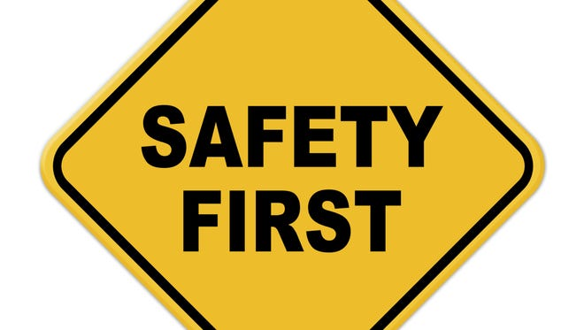 Yellow safety first road sign with rivets