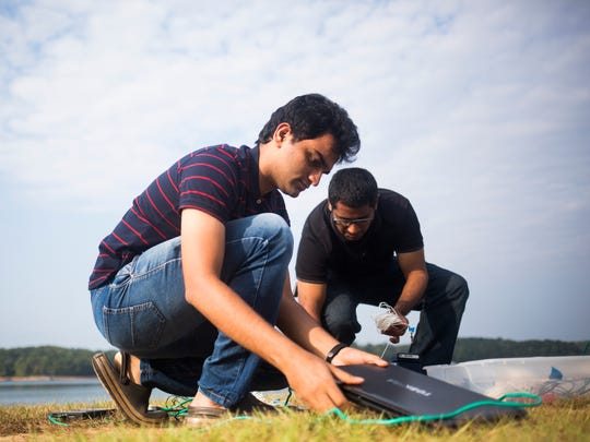 Graduate students Aditya Kamath (left) and Saurab Prabhu (right) work to install monitoring equipment on Clemson University's levee on Monday, September 26, 2016.