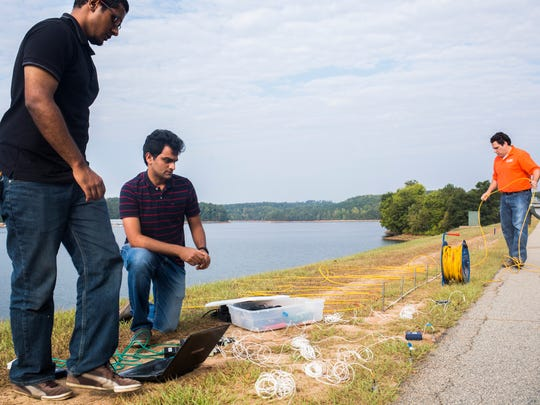 Graduate students Saurab Prabhu and Aditya Kamath (left) and Professor of Environmental Engineering and Earth Sciences, Stephen Moysey, (right) work to install monitoring equipment on Clemson University's levee on Monday, September 26, 2016.