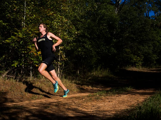 Junior Mason Hazel races his second of six 1,000 meter trail runs in Rocky River Nature Park during Anderson University's cross country practice on Tuesday, October 11, 2016.