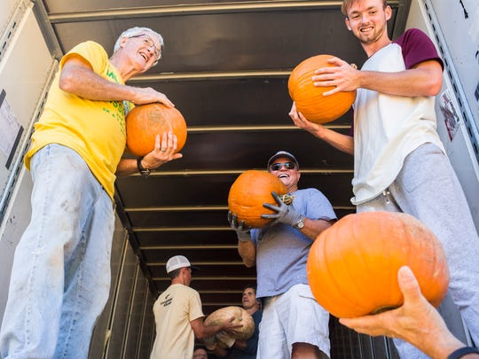 Tim Hennessy, left,  Jim Bowen, center, and Michael Melvin, right, help to unload pumpkins at Trinity United Methodist Church on Wednesday, October 12, 2016 in Anderson.