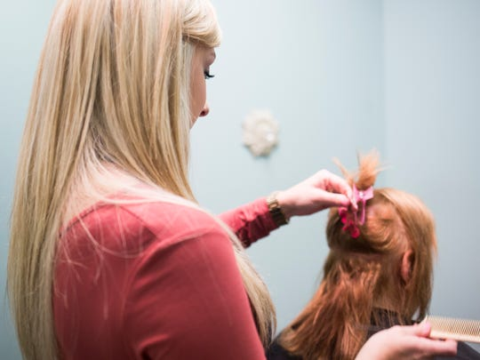 Allie Williams, the 19-year-old owner of Salon 97, works on client Kim Bullard's hair on Friday in Easley.