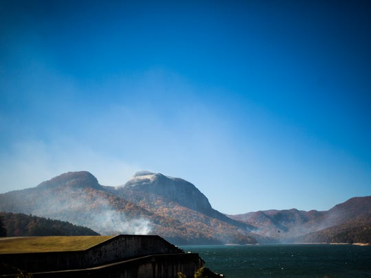 Smoke rises from the back of Table Rock mountain as