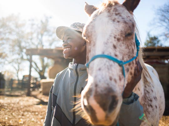 Anderson County Alternative School eighth grader Asaad Stewart, 13, smiles after successfully completing a trust exercise with his horse, Hercules, as a part of an equine therapy class at Dark Horse Farm on Thursday, December 1, 2016 in Belton.
