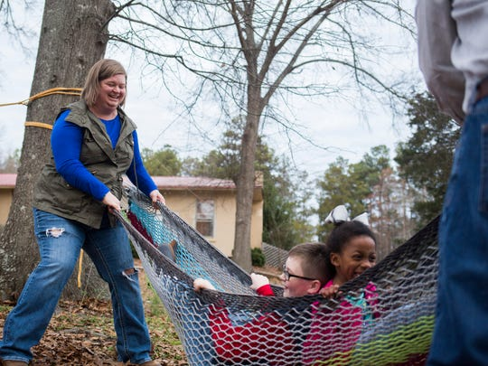 Hannah Vernon, left, and her husband, Jamie Vernon, swing their children in a hammock Thursday at their home in Starr.