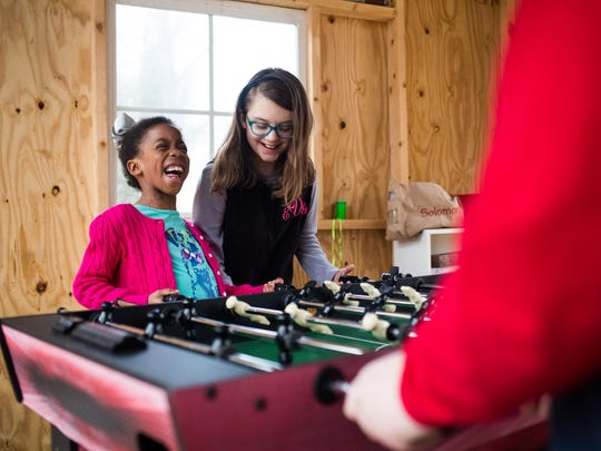 Delainey Vernon, 7, and her sister Emma Grace Vernon, 9, laugh as they score a point against their brothers in a girls vs. boys game of foosball in their treehouse on Thursday at their home in Starr.