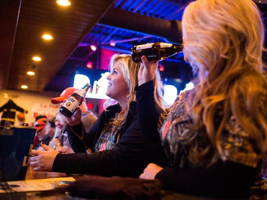 Jada Umbaugh of Anderson, center, drinks a beer while waiting to watch the national championship game at Wild Wing Cafe near Anderson on Monday.