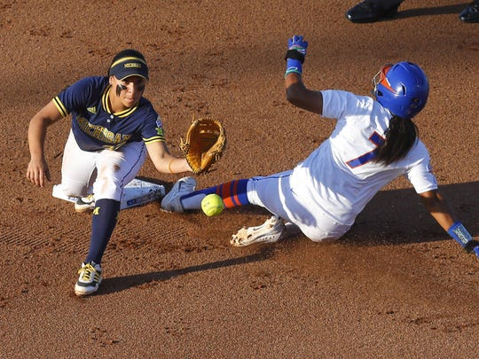 Florida's Kelsey Stewart slides safely into second as Romero takes the throw in a World Series game last season.