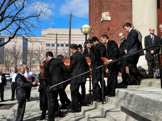 Family members serving as pall bearers bring the casket of Nathan Trapuzzano out of Holy Rosary Catholic Church in Indianapolis following his funeral mass on Saturday morning, April 5, 2014.