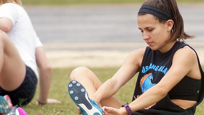 Anderson University's Haylee Love puts on her track shoes before practicing with her teammates Monday afternoon.