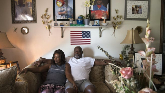 Maritza Ambler and her husband, Javier, sit in the living room under pictures of their son, Javier Antonio Ambler II, at their home in Killeen on Friday. The younger Ambler died in police custody in North Austin on March 28, 2019, after a police chase that started when a Williamson County deputy noticed he did not dim his high beam headlights for oncoming traffic.