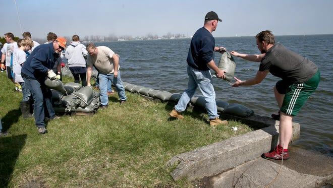 Volunteers sandbag homes in Sodus Point as rising lake waters threaten property on Greig Street.