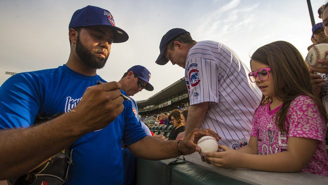 Carlos Pimentel signs a ball for Leah Loeffelholz, 6, of Waukee before the Iowa Cubs home opener Friday, April 17, 2015.