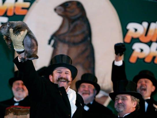 Groundhog handler Ben Hughes holds up Punxsutawney