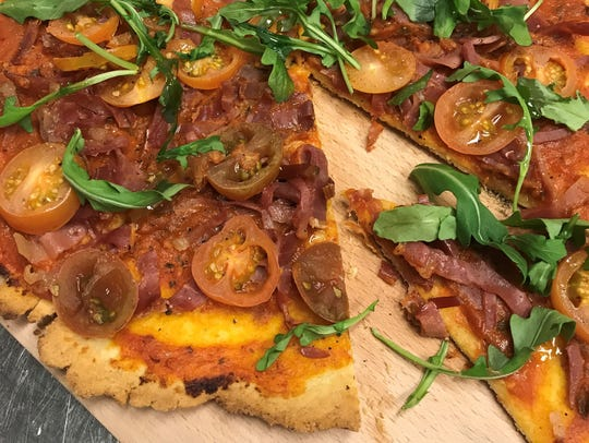 Fresh tomato and arugula gluten-free pizza with prosciutto