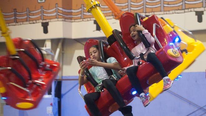 "Emily Sanchez and Natalie Sanchez enjoy the Air Shot ride at The Funplex new ""BoardWalk"" room/section."