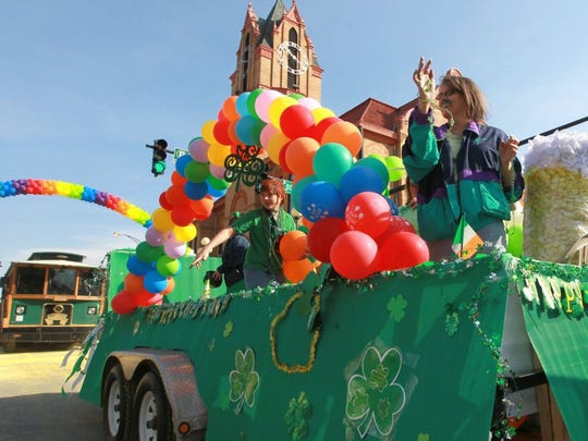 Middy McClure waves from the Pints for People float passing by spectators in the St. Patrick's Day parade.