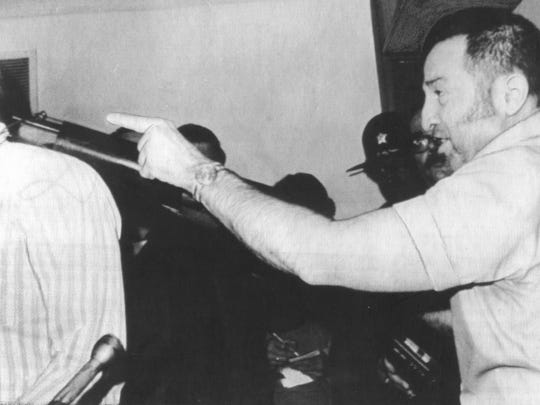 Tony Kiritsis holds a shotgun to the head of his hostage,