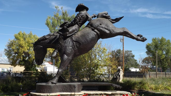 """This statue in Kaycee, Wyoming, is titled """"Good Ride Cowboy."""" It memorializes Chris LeDoux riding horse Stormy Weather in Oklahoma City when he won the 1976 World's Bareback Championship gold buckle. Notice the sculpture is set on top of a guitar, which is inscribed with the words from LeDoux's song, """"Beneath the Western Skies,"""" and depicts the importance music played in his life. LeDoux died in 2005."""