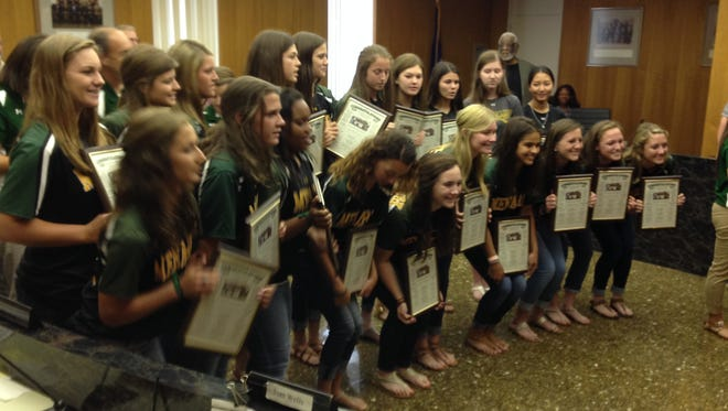 Members of the Menard High School girls softball team hold plaques given to them by the Rapides Parish Police Jury in honor of the team winning the Class 2A state title.