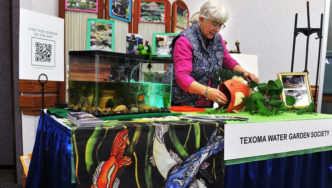 Mary Rhoads sets up the organization's booth at the 19th annual Arts Alive! Home & Garden Festival. The event will return to the MPEC's Ray Clymer Exhibit Hall Feb. 25-26.