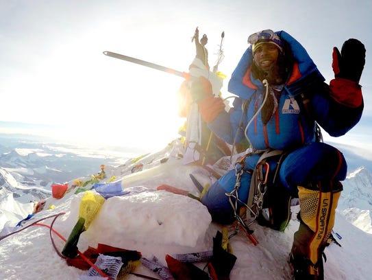 Neal Kushwaha poses at the summit of Mount Everest.