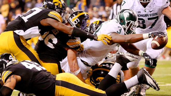 Michigan State running back LJ Scott (3) reaches across the goal line for the go ahead touchdown against Iowa during the Big Ten Championship Game at Lucas Oil Stadium on Dec. 5, 2015.