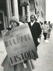 Civil rights activist Rosa Parks, carries a sign protesting cutbacks at General Motors and is followed by Rep.John Conyers Jr. D-Detroit in a picket line in front of General Motors  Corp. Headquarters in 1986.
