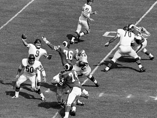 Quarterback Bill Wade (9) of the Chicago Bears gets ready to pass in the second quarter as Los Angeles Rams charge in, led by Roosevelt Grier (76), on Aug. 28, 1965 at Dudley Field.