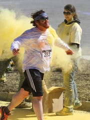 A runner get splattered with yellow during the Do or