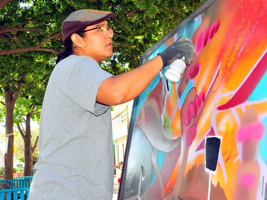 "Artist Saba, a native of Farmington, N.M.,  creates a painting called ""Pueblo Funk"" during the recent Oye Fesitval in downtown Las Cruces. Saba said he is trying to bring awareness to using spray paint as a medium, something he calls ""Arrowsoul Art."""