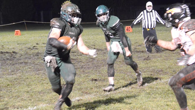 Cedarville's Grant Fountain runs the ball during a game against Munising Friday night. Fountain ran for three touchdowns in the Trojans' 32-8 win.