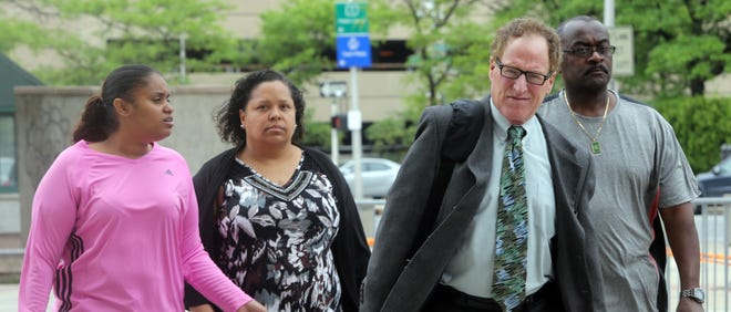 Nicole Diggs, 31, of Yonkers, left, walks into the Westchester County Courthouse, accompanied by her aunt and uncle and her lawyer, in front, in White Plains on Wednesday. Diggs was charged in the death of her daughter, 8-year-old Alayah-Rose Savarese.  The severely disabled Yonkers girl was found dead in her apartment two years ago.
