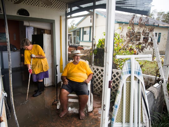 Lisa Marteeny sweeps sludge from one room to the next as her husband, Lee, sits on the front porch on Thursday, Sept. 14, 2017, four days after Hurricane Irma.