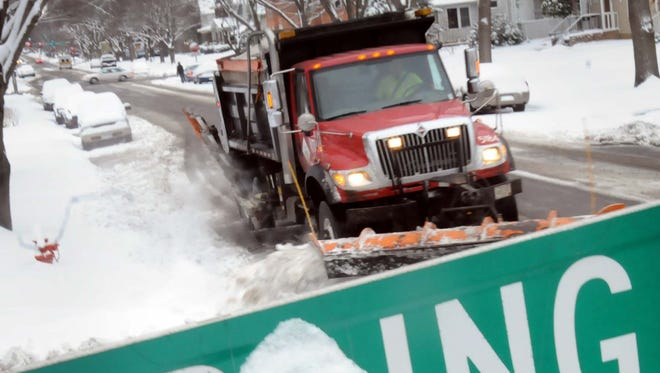 A city plow truck rumbles down a Mankato, Minn. street on Monday, clearing more than six inches of heavy, wet snow that fell overnight. The storm also hit Wisconsin, Illinois and Iowa.