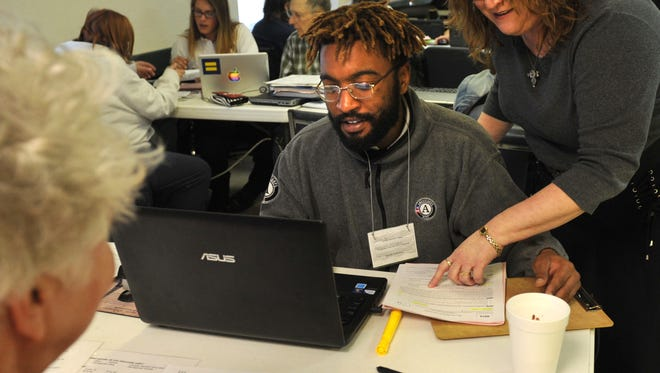 Americorps team member Julian Harris (left) and Volunteer Income Tax Assistance program director Genevieve Anderson review paperwork Thursday while helping families with their taxes.