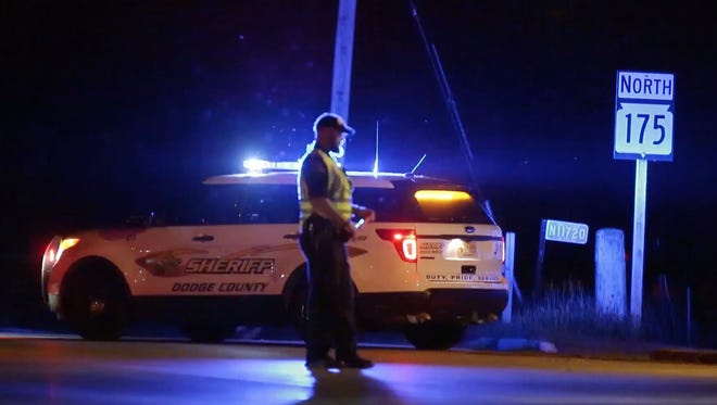 A Dodge County Sheriff's deputy blocks Highway 175 at Highway 49 after a bomb threat was reported at Quad Graphics in Lomira.