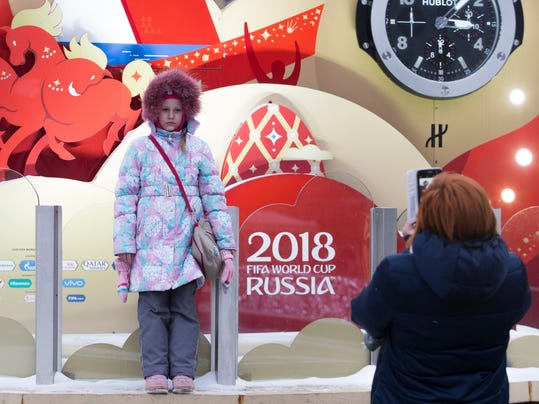 A girl poses for a photo in front of a clock counting down to the first match of the 2018 World Cup, which is installed on Manezh Square, outside the Kremlin in Moscow, Russia, Thursday, Nov. 30, 2017. The Final Draw for the 2018 FIFA World Cup will take place on Friday, Dec. 1, 2017, at the State Kremlin Palace in Moscow. (AP Photo/Denis Tyrin)