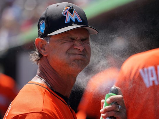 March 21: Marlins manager Don Mattingly sprays sunscreen