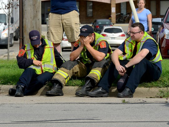 "Lansing firefighters sit on the curb on Cedar Street just north of Jolly Road Wednesday after a fellow firefighter was hit by a vehicle during the ""Fill the Boot"" collection campaign."