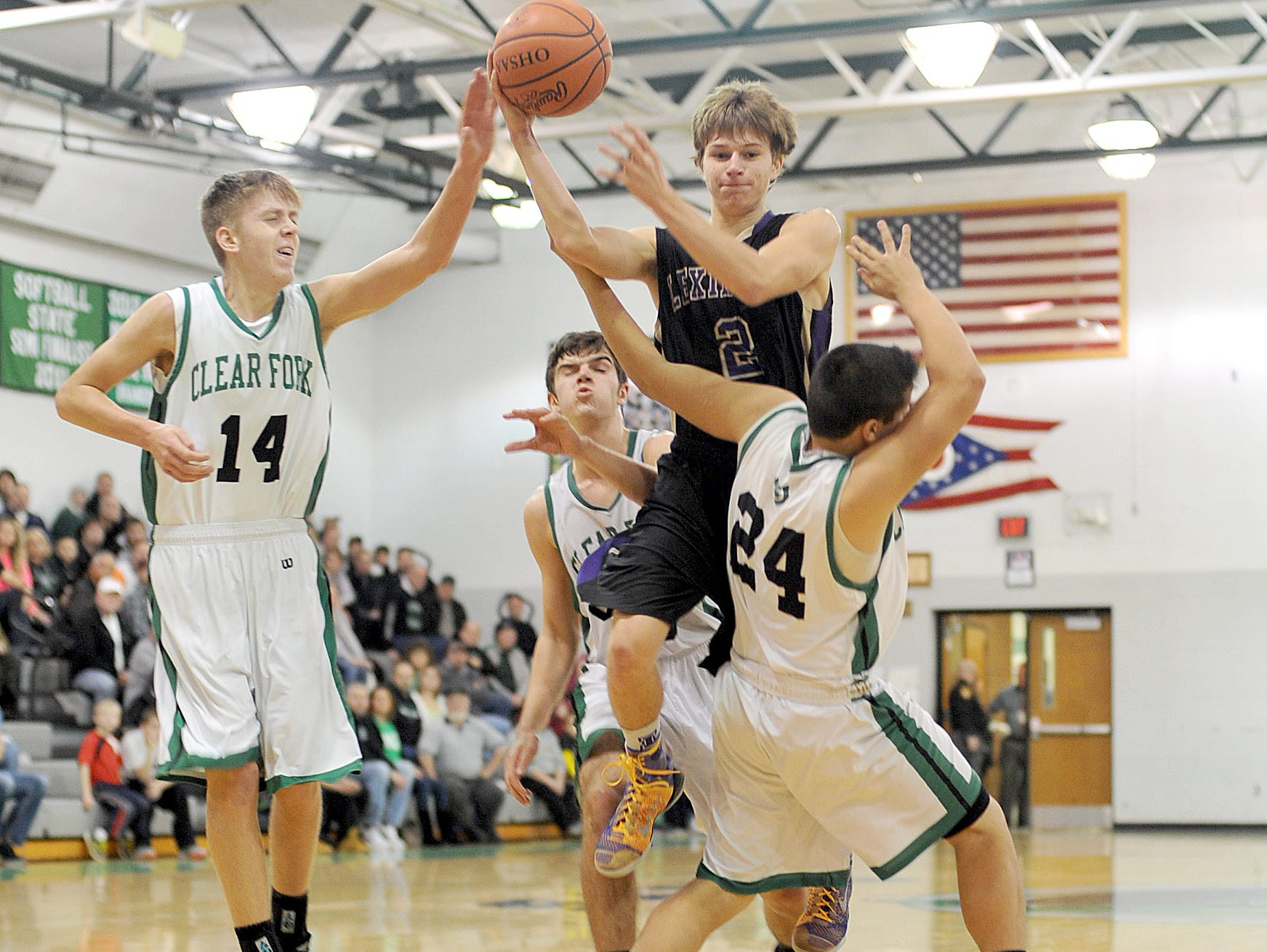 Lexington's Joey Zahn passes the ball as he is surrounded by Clear Fork's Chase Endicott, Chase Barrett and Daniel Spencer on Friday night at Clear Fork High School.