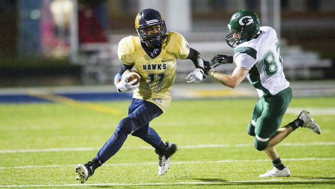 Decatur Central High School freshman Tyrone Tracy (11) rushes the ball upfield as he's chased down by Greenwood High School senior Kyle Mcclarney (82) during the second half of action. Decatur Central hosted Greenwood High School in varsity football action, Friday, October 3, 2014. Decatur Central defeated Greenwood 34-0.
