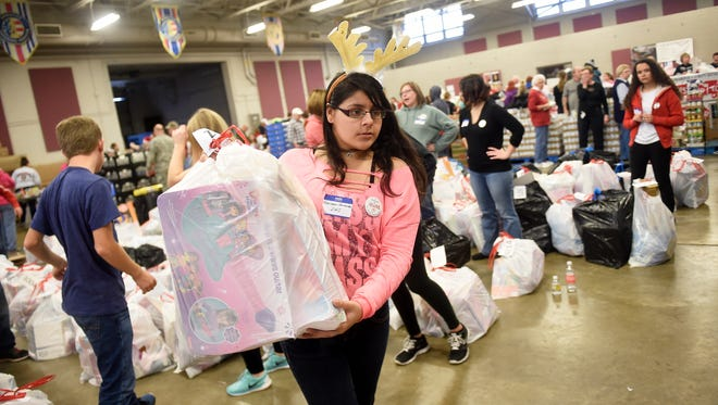 Lebanon High School student and volunteer Karimar Hernandez brings toys and gifts to Operation Santa recipients on Dec 22. The annual charity filled the National Guard Readiness Center in South Lebanon Township with toys, food and clothing. Operation Santa helped 1,892 people.