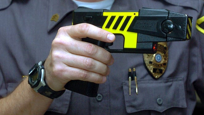 An officer holds a stun gun used by his police department in a Farmington, Conn.