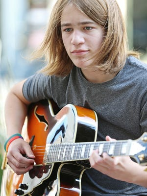 Graham Helft, 15, plays classic jazz along Massachusetts Avenue, Thursday, June 16, 2016. Helft, a patient of Riley Hospital for Children, busks in Indianapolis and will donate his earnings to the hospital's music therapy program at the end of summer.