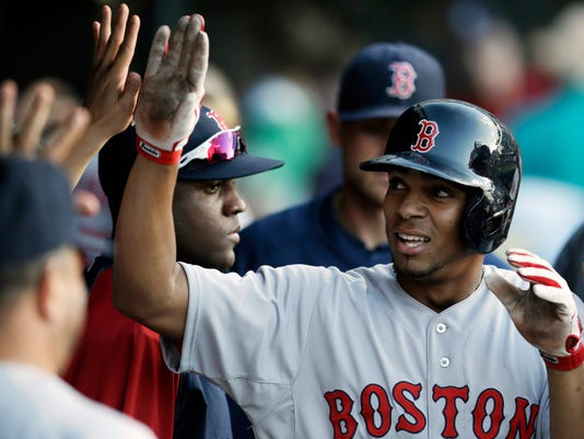 Boston Red Sox's Xander Bogaerts is congratulated by teammates after hitting a solo home run off Cleveland Indians relief pitcher T.J. House in the third inning of a baseball game, Tuesday, June 3, 2014, in Cleveland. (AP Photo/Tony Dejak)