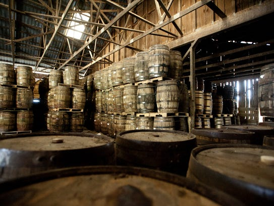 Oak barrels holding whiskey age in an old cow barn