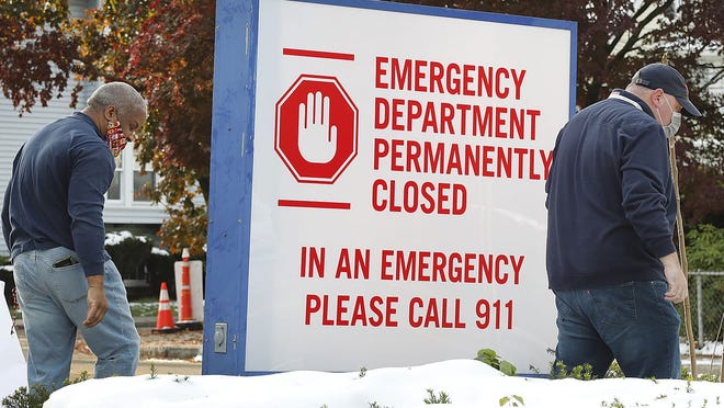 Workers unveil signs on Sunday, Nov. 1, warning that Quincy Medical Center has permanently closed.