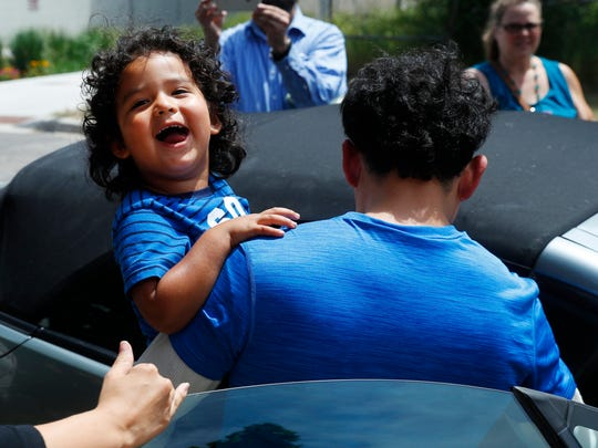 Ever Reyes Mejia, of Honduras, carries his son to a vehicle after being reunited and released by United States Immigration and Customs Enforcement in Grand Rapids, Mich., Tuesday, July 10, 2018. Two boys and a girl who had been in temporary foster care in Grand Rapids were reunited with their Honduran fathers after they were separated at the U.S.-Mexico border about three months ago.